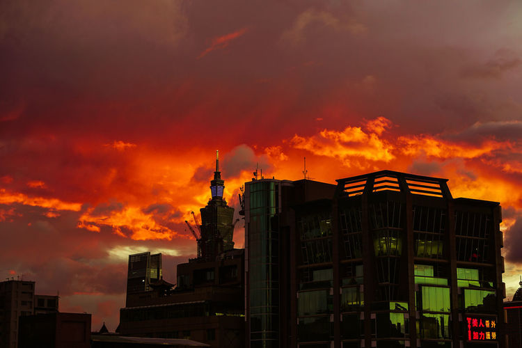 Low angle view of buildings against dramatic sky during sunset