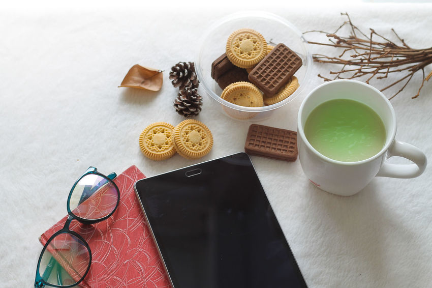 Lazy afternoon Macha Tea The Week on EyeEm EyeEm Selects Digital Tablet Technology Book Red Book Autumn Theme Winter Theme Afternoon Snack Leisure Activity Afternoon Tea Top View Acorns Cookies Copy Space Space For Text No People Reading Glasses Reading & Relaxing Eyeglasses  High Angle View White Background Close-up Tea Personal Accessory Hardcover Book Literature Touch Screen E-reader