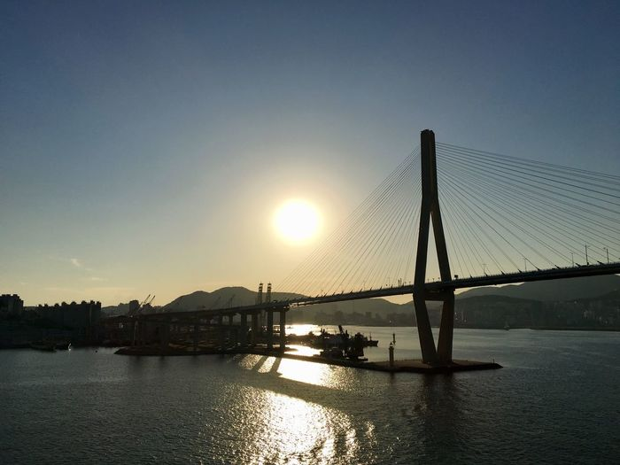 View of suspension bridge over river at sunset