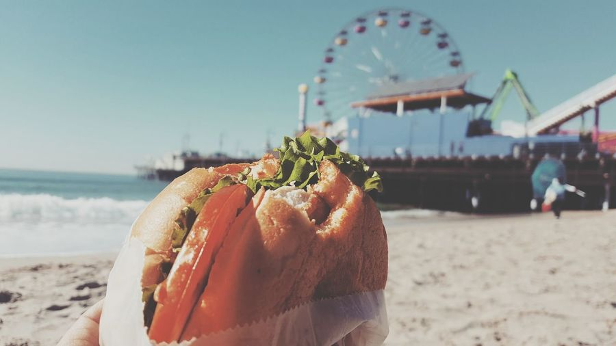 Person Holding Burger At Beach Against Sky