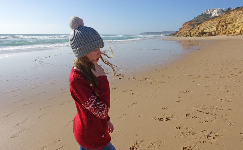 Girl in a bobble hat on the beach in portugal in winter