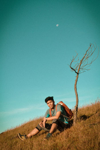 Young man sitting on field against clear sky