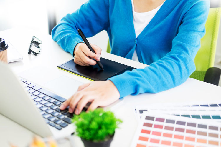 Midsection of design professional using graphics tablet and laptop on desk