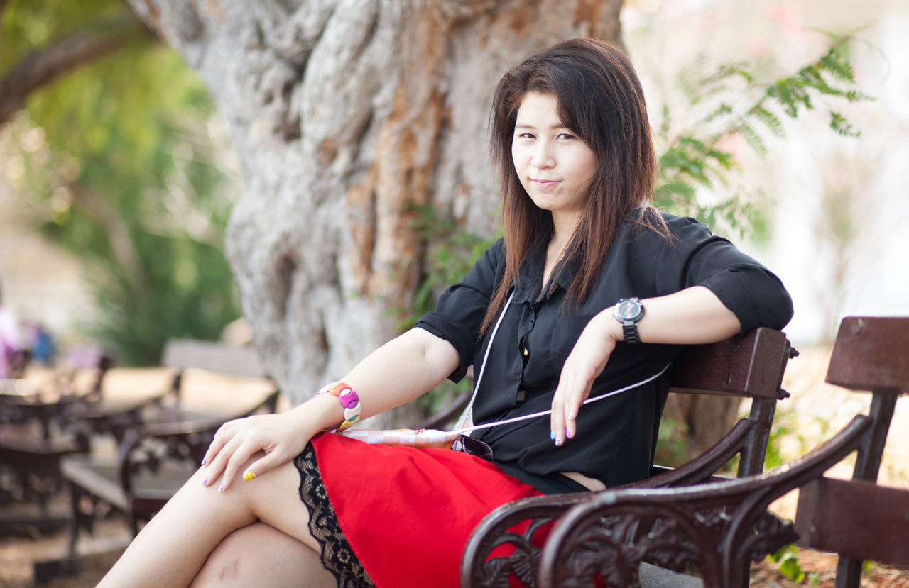 Close-Up Portrait Of Young Woman Sitting On Bench