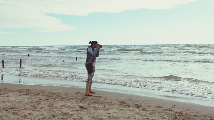 Full Length Of Woman Photographing At Beach Against Sky