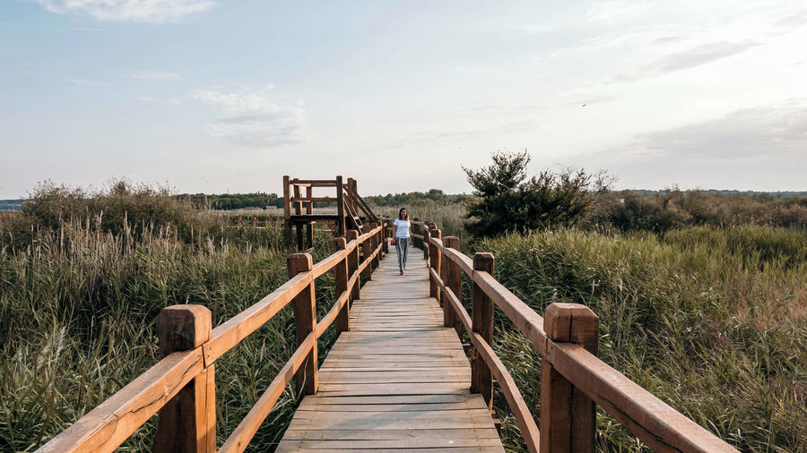 Young woman on wooden pathway in nature park. spring, summer, tourism, travel.