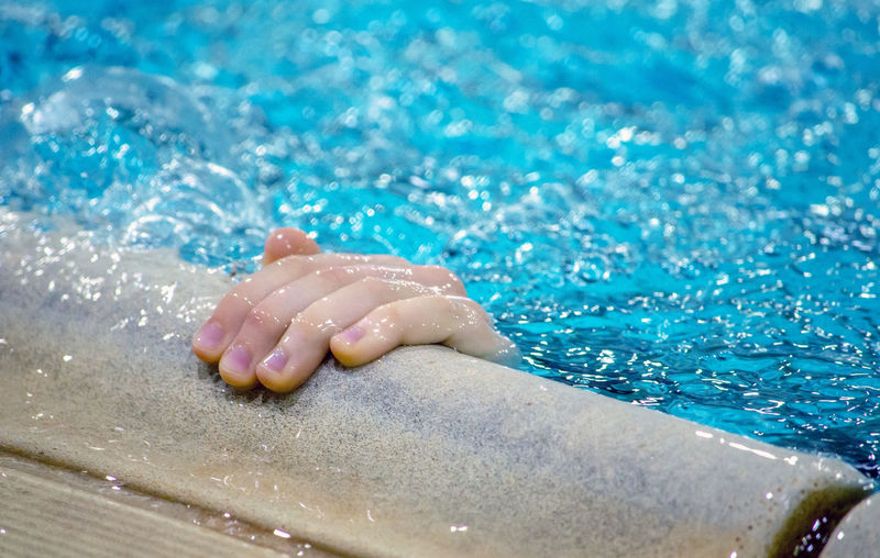 A small hand reaches out of a swimming pool to grasp the edge perhaps to keep from drowning