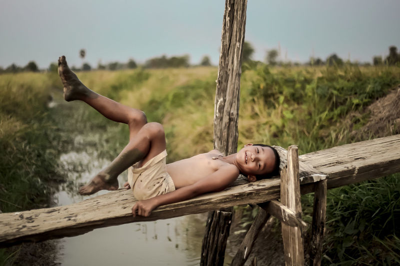 Portrait Of Shirtless Boy Lying On Wood At Farm
