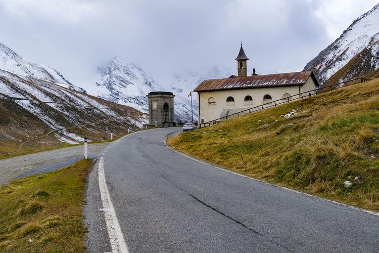 Road leading towards church against sky