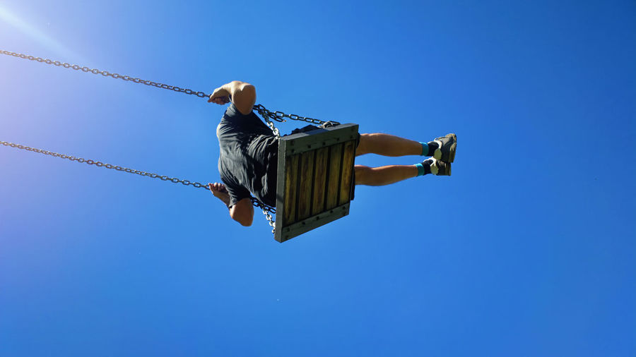 Low angle view of man swinging against clear blue sky