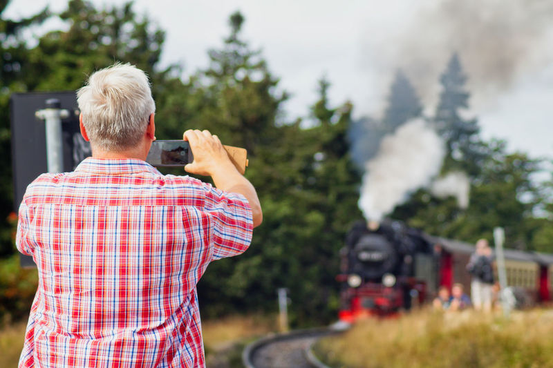 Holiday Moments Brocken Brockenbahn Steam Engine Steam Train Technology Photography Themes Photographing Rear View Camera - Photographic Equipment Men Activity Holding Real People Focus On Foreground Photographic Equipment Waist Up Males  Nature Leisure Activity Day Gray Hair People Mature Adult Camera Wireless Technology Digital Camera Mature Men Photographer Outdoors A New Perspective On Life Capture Tomorrow
