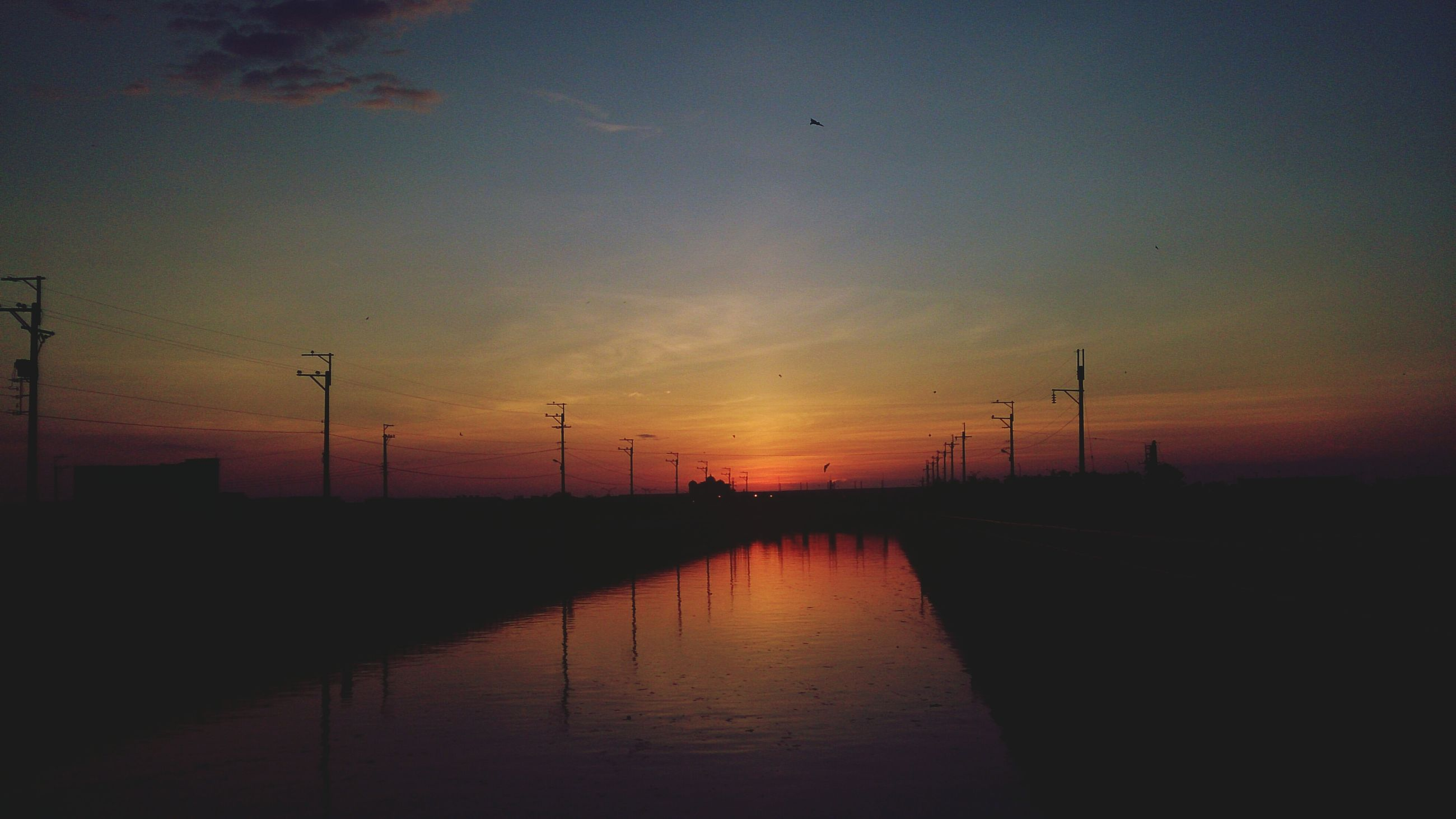 sunset, water, silhouette, reflection, waterfront, sky, tranquility, tranquil scene, scenics, orange color, beauty in nature, nature, lake, river, idyllic, dusk, outdoors, no people, electricity pylon, connection