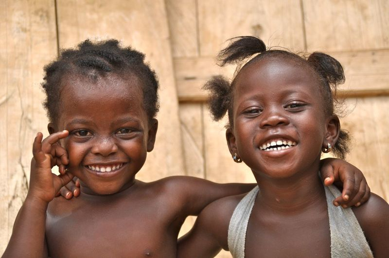 Close-up portrait of cheerful sisters standing outdoors