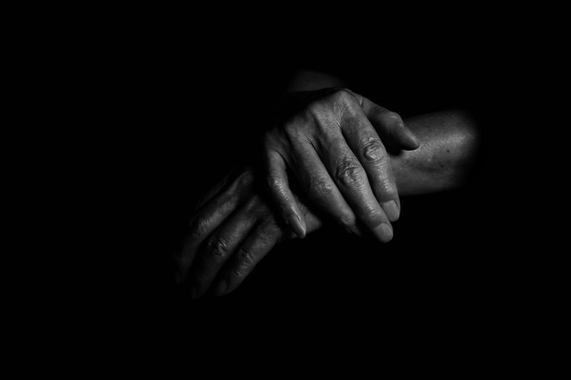 Close-Up Of Human Hands Over Black Background