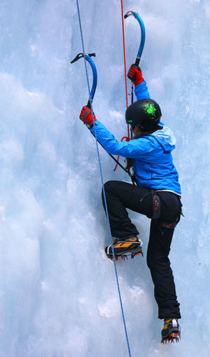 Rear View Full Length Of Woman Ice Climbing