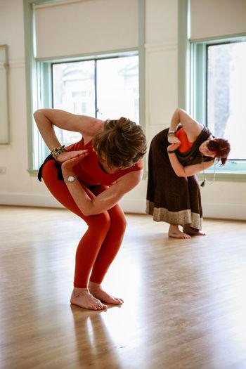 Nia Full Length Indoors  Women Exercising Practicing Lifestyles Flexibility Skill  Dancing Females Bending Balance Healthy Lifestyle People Education Real People Ballet Two People Ballet Dancer Wood Flooring