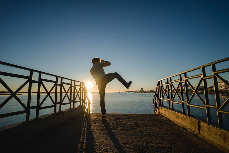 Man Kicking On Pier At Beach Against Sky