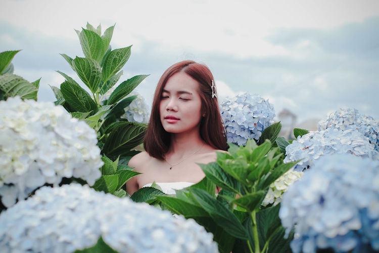 Young woman with eyes closed amidst flowering plants