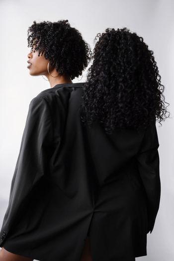 Two beautiful dark skin women wearing same jacket