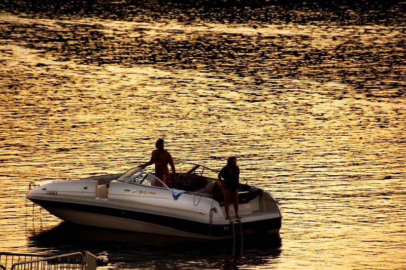 Boat in water at sunset