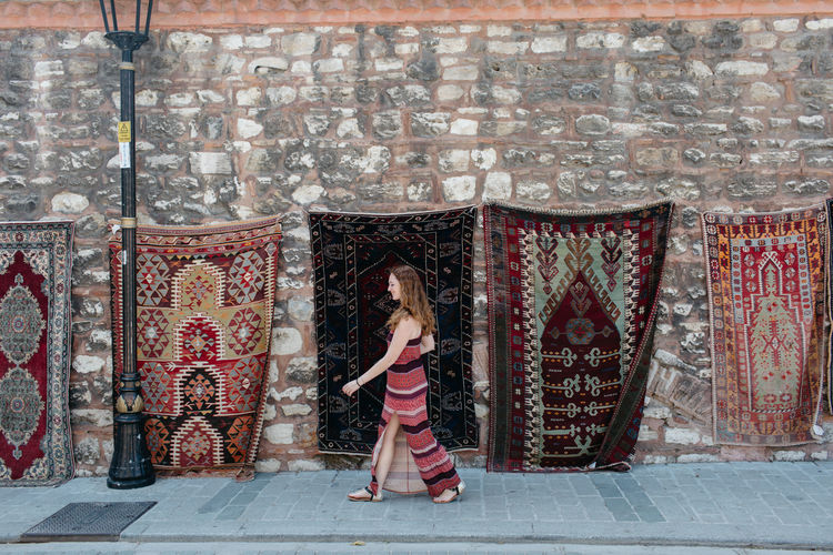 Woman Walking By Carpets Against Wall