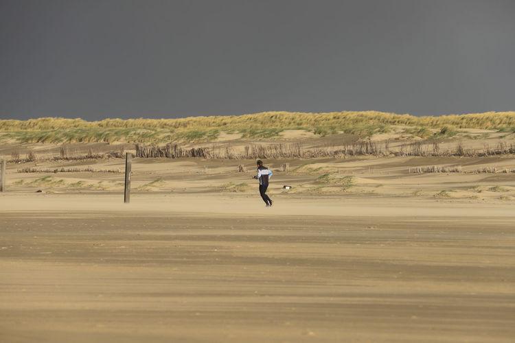 Man Running At Beach Against Clear Sky