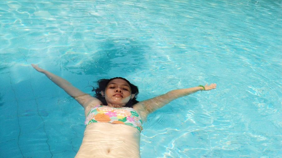 High angle portrait of woman floating in swimming pool