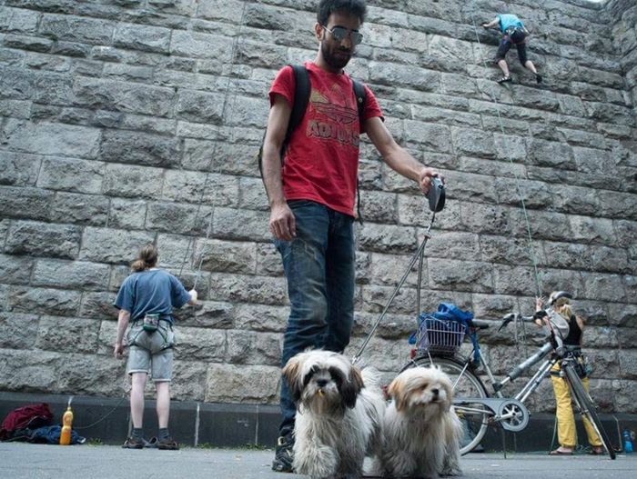 People with dog standing against wall
