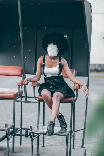 Full Length Of Woman With Face Covered By Bandage Sitting On Chair