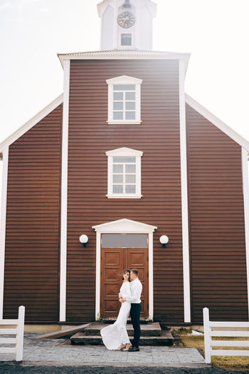 Woman standing outside house against building