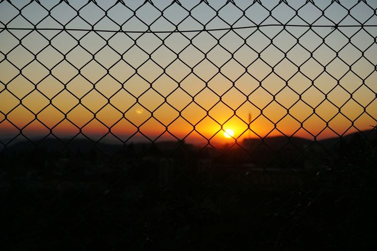 Silhouette chainlink fence on field against sky during sunset