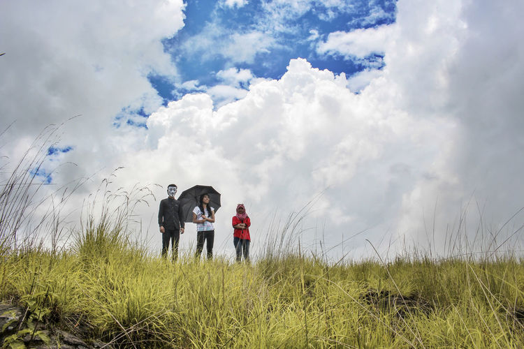 Low Angle View Of Friends Standing On Grassy Field Against Cloudy Sky