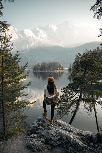 Woman standing on rock while looking at sunrise over mountain