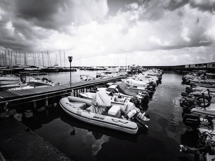 High angle view of boats moored at harbor against sky