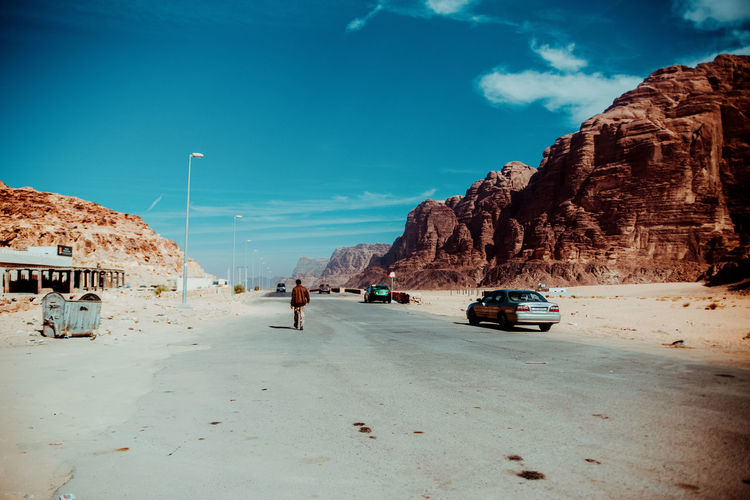 Cars on road by rock formation against sky