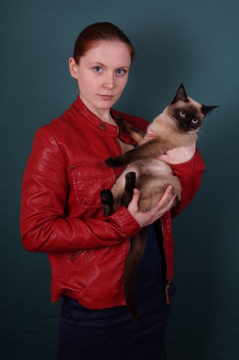 Portrait of young woman holding siamese cat against gray background