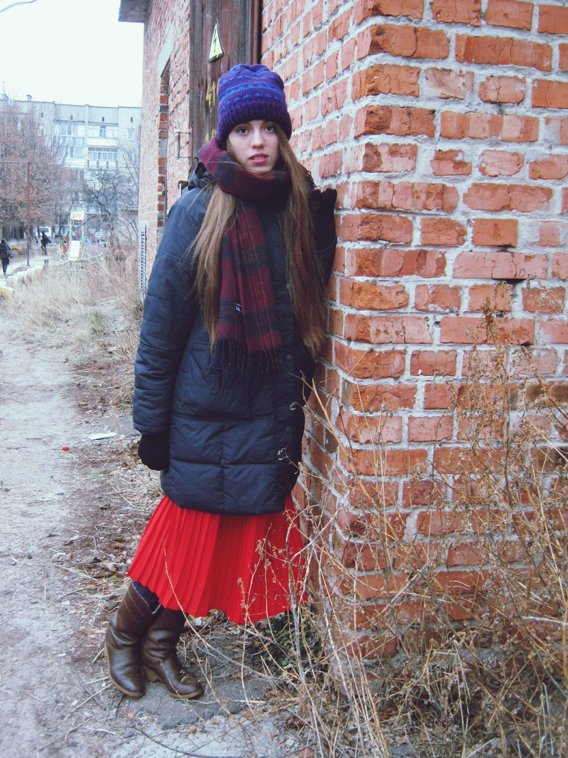 young adult, looking at camera, portrait, front view, lifestyles, casual clothing, person, young women, building exterior, standing, leisure activity, brick wall, red, architecture, built structure, full length, smiling