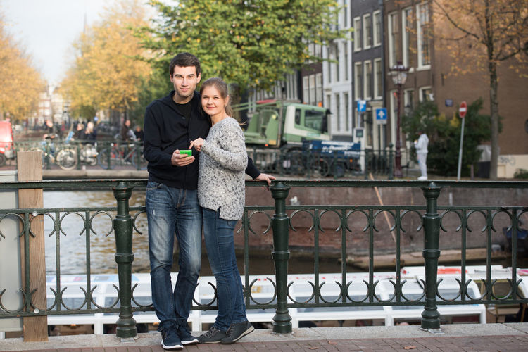 Smiling Young Couple Using Smart Phone In City