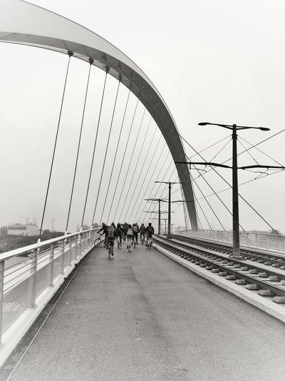 People walking on bridge against clear sky