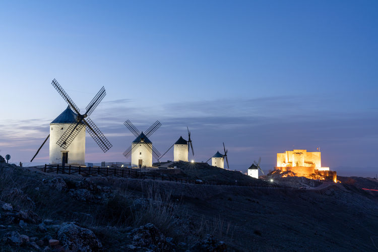 Traditional windmill on street by building against sky