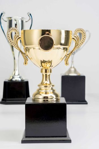 Variety of Trophy Cup on white background AWARD Success Achievement Trophy Winning Gold Colored Indoors  Shiny Competition Metal Still Life Gold No People Medal Focus On Foreground Studio Shot Close-up Table Single Object Pride