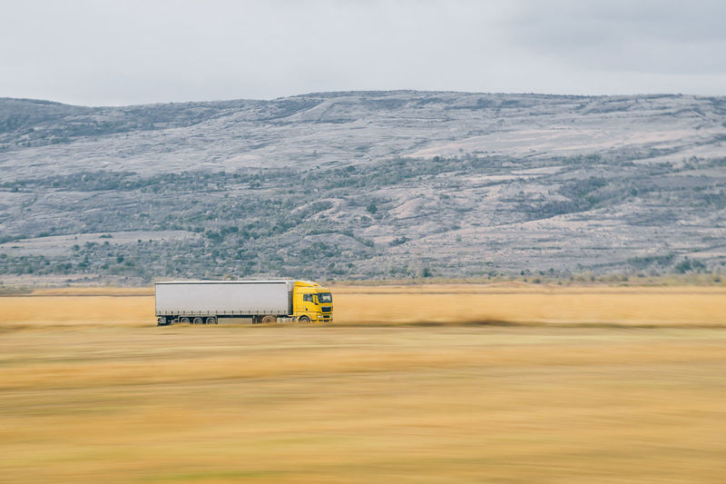 Train speed: 90 km/h. Trailer speed: aprox 100 km/h. Camera speed 1/13. Max zoom 200mm. Conclusion: I was really bored. Vehicle Heavy Vehicle Motion Motion Blur Truck TIR Transportation Mountain Rural Scene Yellow Landscape Vehicle Trailer Commercial Land Vehicle Van - Vehicle