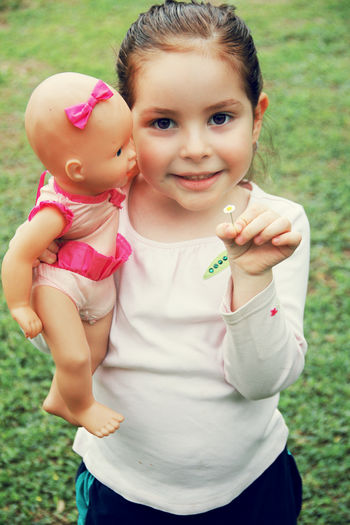 Portrait of cute girl holding tiny flower and doll on field