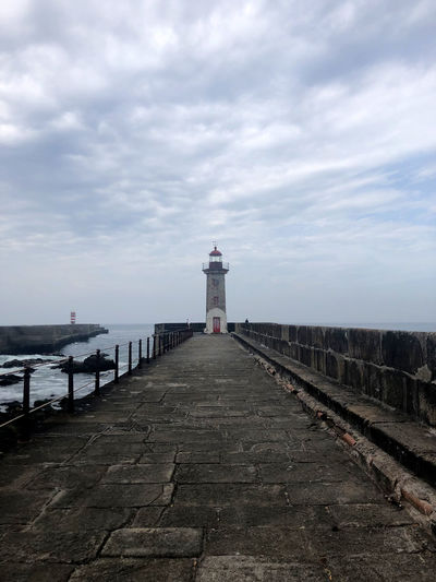 Lighthouse on footpath by sea against sky