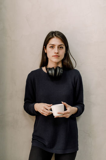 Portrait of a young woman holding coffee cup against wall