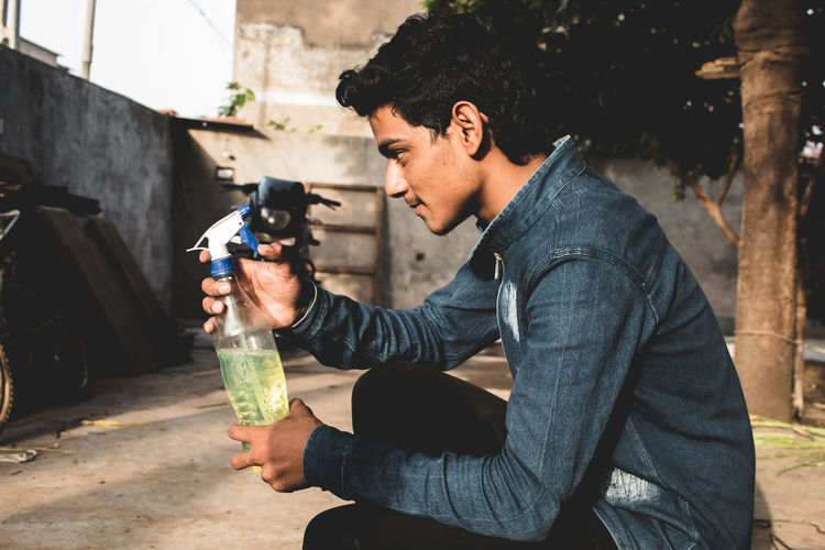 Side view of teenage boy holding bottle while crouching outdoors
