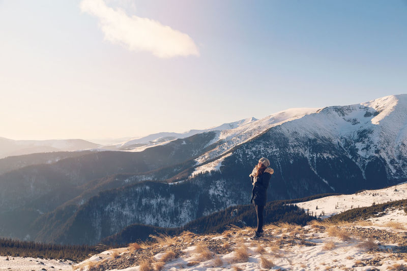 Winter portrait of a beautiful woman admiring the mountain view Hiking Admiring The View Beauty In Nature Hiker Hobby Leisure Activity Mountain Mountain Range Nature One Person Real People Snow Standing Sunrise Winter