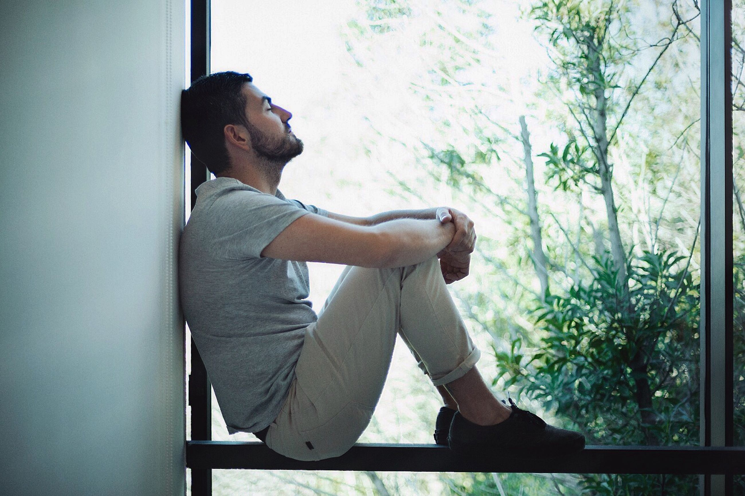 lifestyles, young adult, leisure activity, indoors, casual clothing, full length, side view, sitting, standing, window, holding, three quarter length, tree, young men, person, relaxation, day