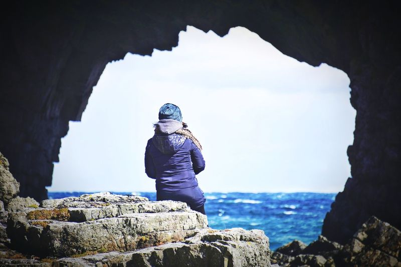 Rear view of woman sitting on rock at beach seen through cave