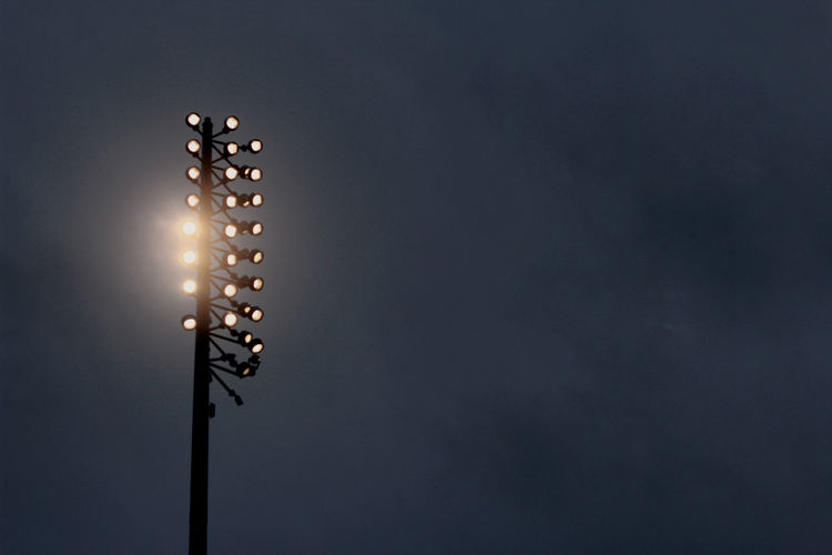 Low angle view of illuminated flood light against sky at night